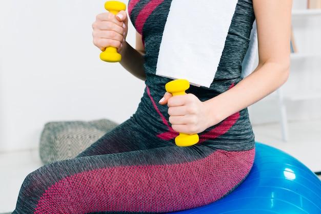 Section médiane de la jeune femme faisant de l'exercice avec des haltères jaunes