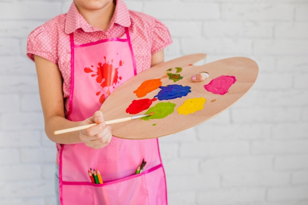 Section médiane d'une jeune fille vêtue d'un tablier rose mélangeant la peinture dans une palette avec un pinceau