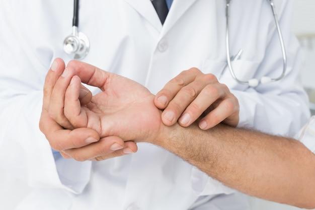 Section médiane d'un médecin prenant le pouls d'un patient