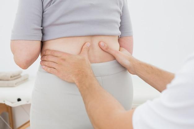 Section médiane d'un physiothérapeute examinant womans retour