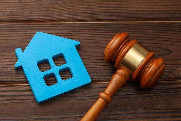 Section de propriété après un divorce ou l'achat ou la vente d'une maison aux enchères. maison bleue et marteau de juge