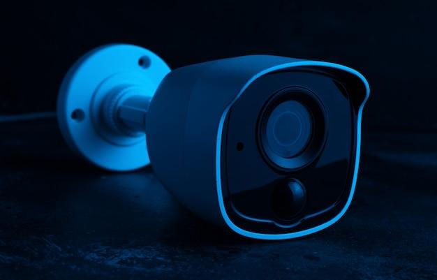 Sécurité de la caméra sur un mur sombre en lumière bleue.
