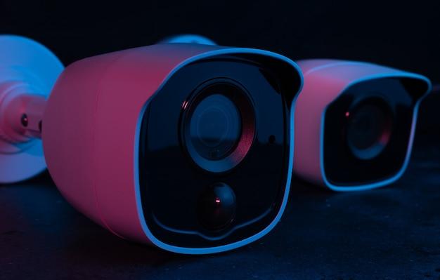 Sécurité de la caméra sur une surface sombre en lumière rose.