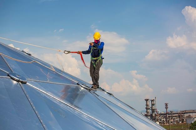 Sécurité de la hauteur d'accès par corde des travailleurs masculins se connectant à un harnais de sécurité à nœud, se clipsant dans les systèmes de point d'ancrage antichute et de retenue contre les chutes de toit prêts à monter, dôme de réservoir d'huile de chantier de construction
