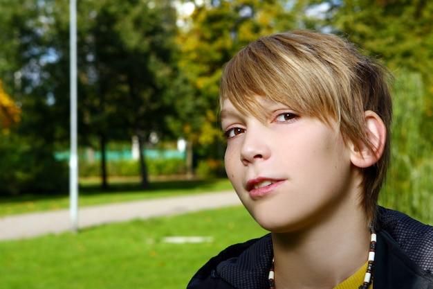 Séduisant, blond, garçon, poser, dans parc