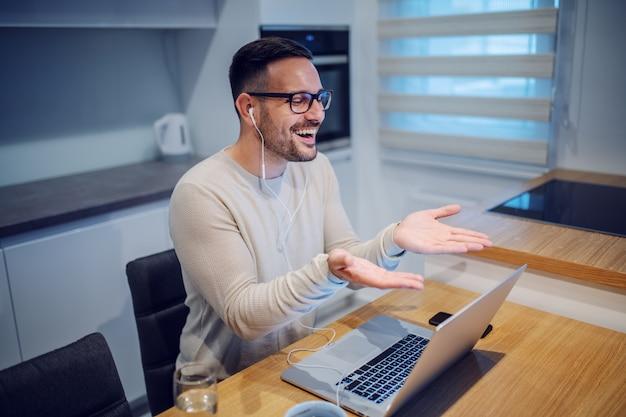 Séduisant homme caucasien souriant assis à table à manger dans la cuisine et avoir un appel vidéo avec sa petite amie. sur la table sont un ordinateur portable, un verre d'eau et une tasse de café.