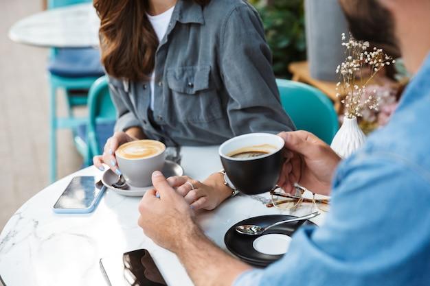 Séduisant jeune couple amoureux en train de déjeuner assis à la table du café à l'extérieur