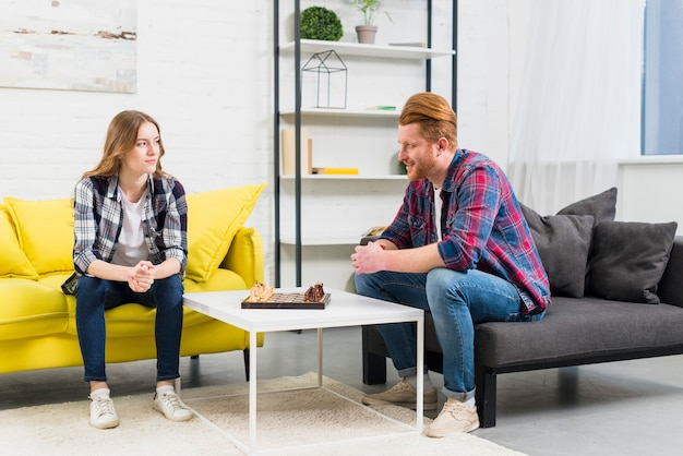 Un séduisant jeune couple se regardant avec un échiquier sur une table