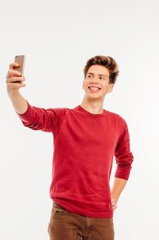 Séduisant jeune homme adolescent fait un selfie avec smartphone sur