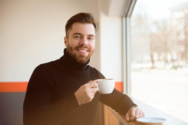 Séduisant jeune homme d'affaires, boire du café assis à la table du café.