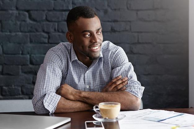 Séduisant jeune homme d'affaires prospère, boire du café assis à la table de café avec une tasse