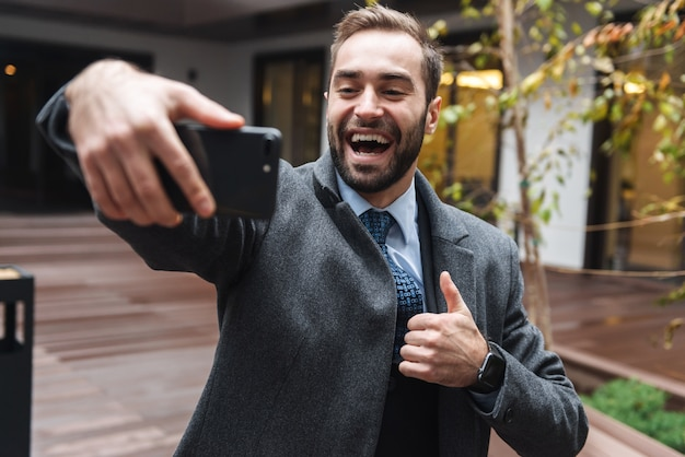 Séduisant jeune homme d'affaires souriant portant costume marchant à l'extérieur, prenant un selfie