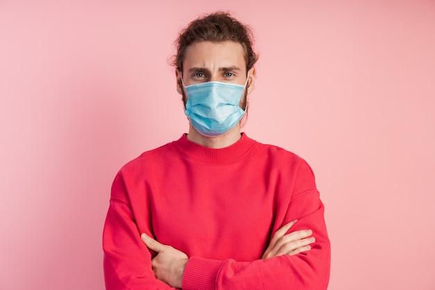 Séduisant, jeune homme aux bras croisés et un masque de protection
