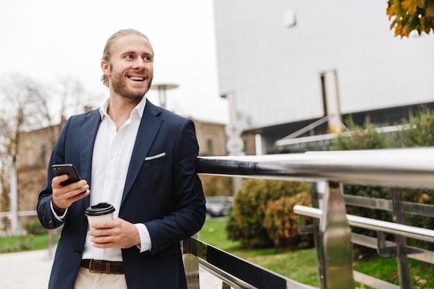 Séduisant jeune homme aux cheveux blonds souriant en tenue de soirée tenant une tasse de café à emporter et utilisant un téléphone portable tout en se tenant à l'extérieur dans une rue de la ville