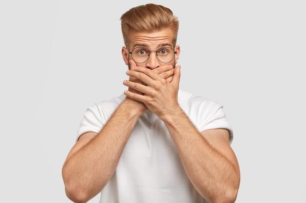 Séduisant jeune homme avec coupe de cheveux à la mode, couvre la bouche, étant muet