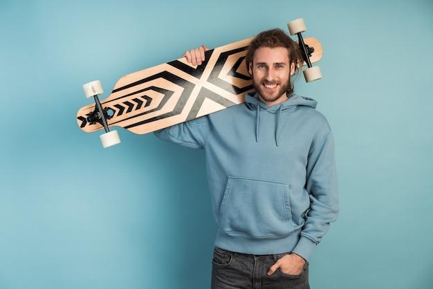 Séduisant, jeune homme dans un pull à capuche tient un patin sur son épaule.