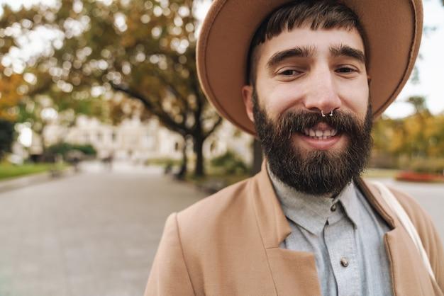 Séduisant jeune homme élégant portant un chapeau souriant et regardant devant tout en marchant à l'extérieur