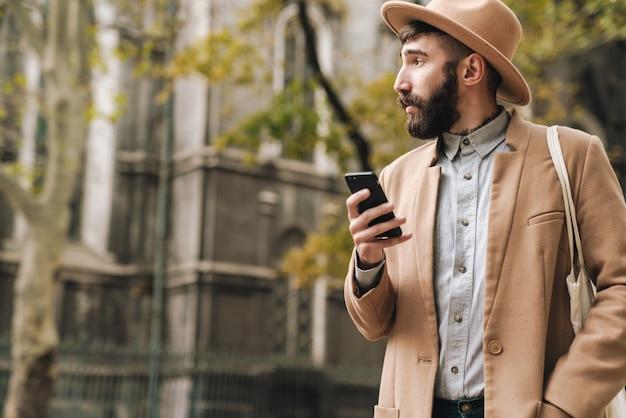 Séduisant jeune homme élégant portant un chapeau tenant un téléphone portable tout en marchant à l'extérieur