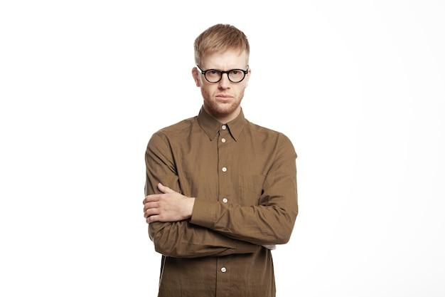 Séduisant jeune homme européen confiant avec des bras croisés de chaume sur sa poitrine, ayant un regard méfiant sérieux, posant en posture fermée, ce qui signifie son aversion, son mécontentement ou son entêtement