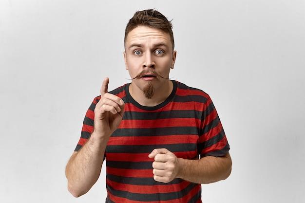 Séduisant jeune homme avec moustache et barbe de guidon regardant la caméra avec un regard fasciné, poiting index vers le haut, montrant quelque chose d'étonnant sur le mur de fond blanc, ouverture de la bouche