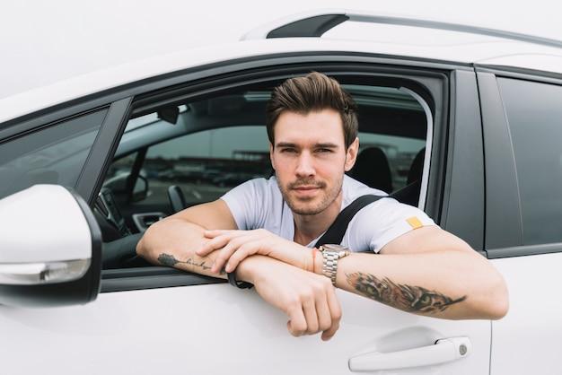 Un séduisant jeune homme regarde par la fenêtre de la voiture
