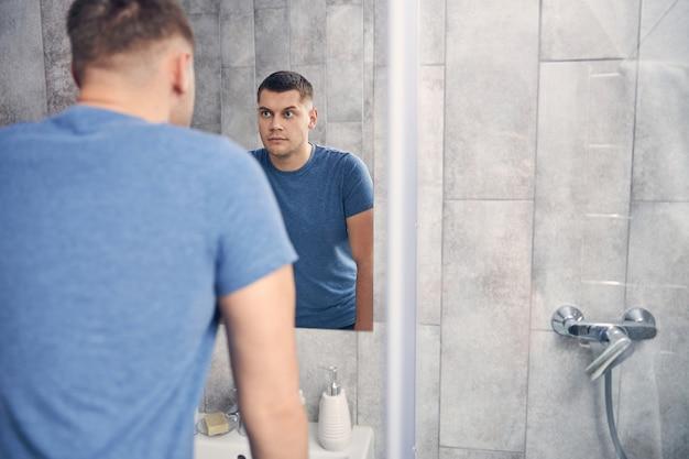 Séduisant mâle brune en t-shirt bleu passant du temps près de l'évier tout en regardant son reflet dans le miroir