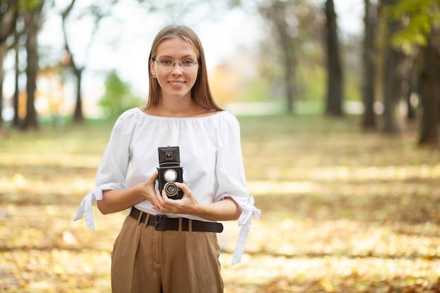 Séduisante belle jeune fille tenant rétro vintage caméra de réflexion à double objectif dans le parc de l'automne