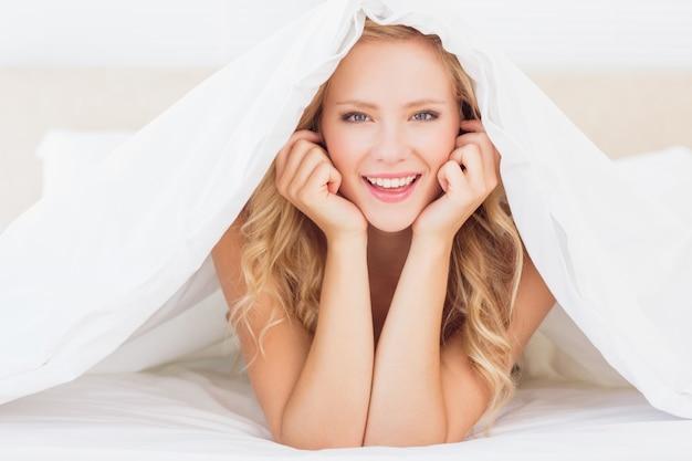Séduisante blonde souriante à la caméra sous la couette