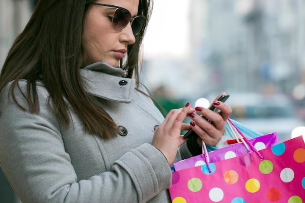 Séduisante brune avec des lunettes de soleil et des sacs à provisions colorés à l'aide de son téléphone intelligent