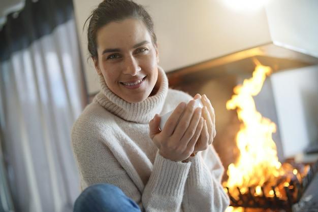 Séduisante brune se réchauffant par le feu avec une boisson chaude