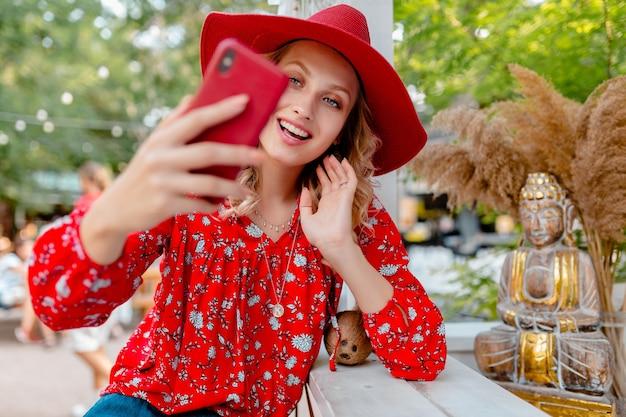 Séduisante élégante femme souriante blonde en chapeau rouge paille et chemisier tenue de mode d'été prenant selfie photo sur caméra smart phone cafe