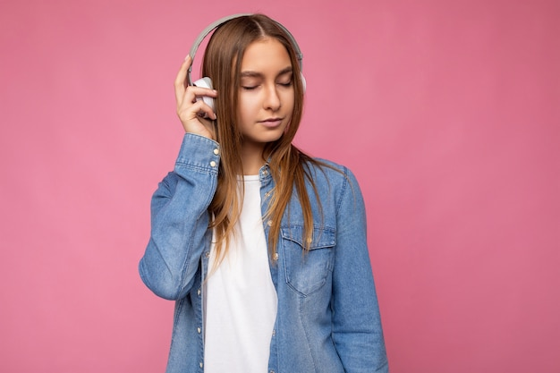 Séduisante avec des émotions sincères jeune femme blonde portant une chemise en jean bleu et un t-shirt blanc