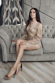 Séduisante femme en barboteuse lacée beige et talons hauts sur canapé