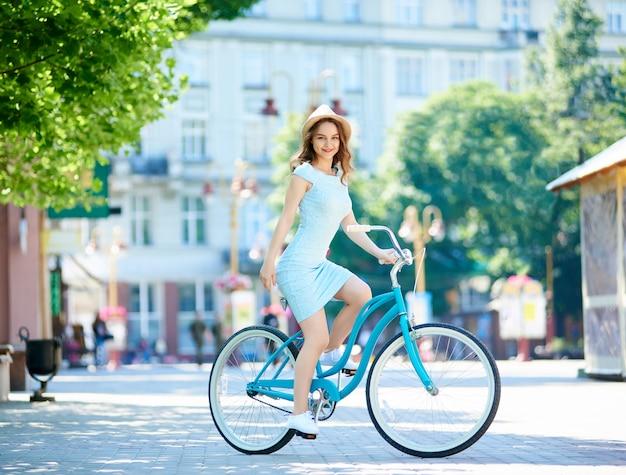 Séduisante femme brune heureuse à vélo dans la ville en visitant