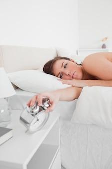 Séduisante femme brune se réveiller avec une horloge en position couchée