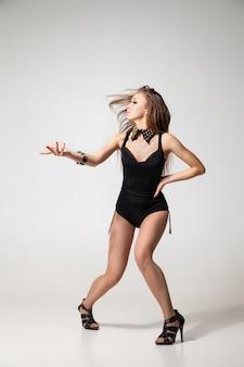 Séduisante femme danse go-go posant sur fond gris