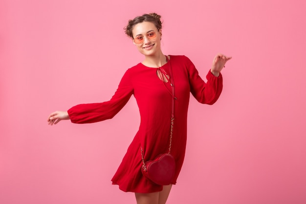 Séduisante femme élégante souriante heureuse en robe à la mode rouge sautant en cours d'exécution sur un mur rose isolé, tendance de la mode printemps été, saint valenite's day, humeur romantique fille flirty
