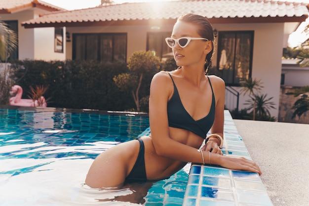 Séduisante femme gracieuse dans des boucles d'oreilles jaunes élégantes avec un corps parfait posant dans la piscine pendant les vacances sur le complexe de luxe