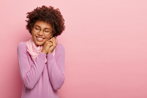 Séduisante femme heureuse avec une coiffure afro, sourit joyeusement, exprime la positivité, garde les yeux fermés du plaisir, a un sourire agréable, porte des lunettes transparentes et un pull, des modèles à l'intérieur sur un mur rose