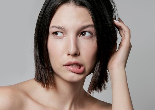 Séduisante femme posant avec un visage idiot