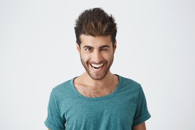Séduisante et gaie jeune homme avec barbe et coupe de cheveux élégante portant un t-shirt bleu clignant des yeux avec plaisir ayant une expression heureuse. expressions faciales et concept d'émotions de personnes