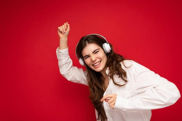 Séduisante heureuse jeune femme brune souriante portant chemise blanche et lunettes optiques