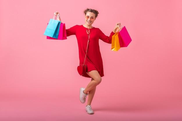 Séduisante heureuse souriante femme élégante accro du shopping en robe rouge à la mode tenant des sacs colorés sur un mur rose isolé, vente excité, tendance de la mode printemps été