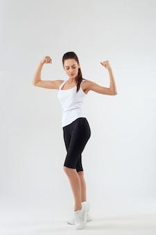 Séduisante jeune adulte sportswear posant sur le mur gris.