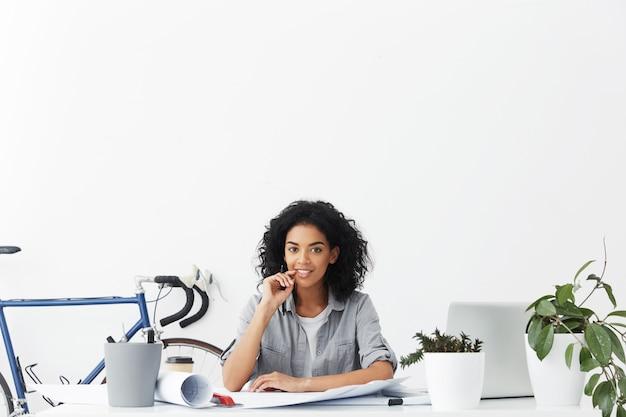 Séduisante jeune architecte métisse positive travaillant à domicile