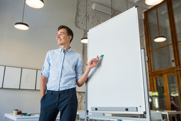 Séduisante jeune bel homme souriant debout au tableau blanc vide avec marqueur