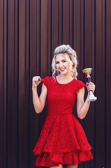 Séduisante jeune blonde dans une robe rouge tenant une coupe du gagnant dans ses mains sur un fond marron.