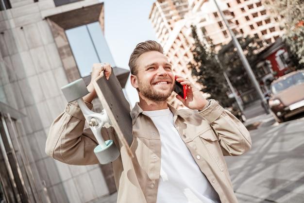 Séduisante jeune blonde souriante tenant une planche à roulettes sur les épaules dans la rue de la ville, debout parmi les bâtiments en verre. porte une tenue en jean. un skateur sportif et élégant parle sur un téléphone portable en riant.