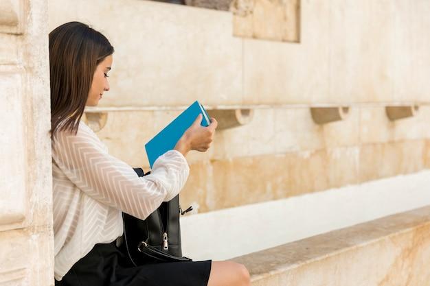 Séduisante jeune brune plaçant un livre dans un sac à dos