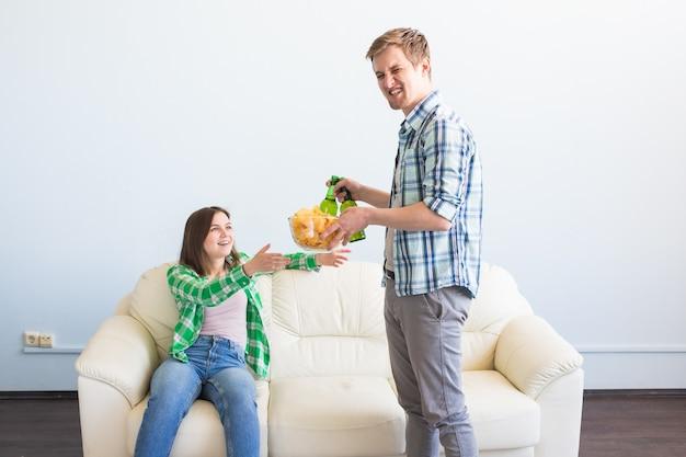 Séduisante jeune couple aimant boire de la bière à la maison.